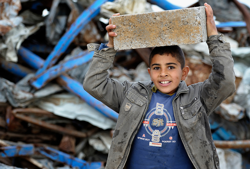 Mohamed Ihab, 12, carries a new construction block in front of a pile of twisted rubble left from the Israeli bombing of his family's farm in Johor Al-Deek, a section of the Bureij refugee camp in Gaza. The farm is being reactivated today with help from a new well and water pump provided by Dan Church Aid--a member of the ACT Alliance--to replace a well and pump destroyed by the Israeli military during Operation cast Lead.