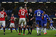 Chris Smalling of Manchester United is booked by Referee Michael Oliver during the Barclays Premier League match between Chelsea and Manchester United at Stamford Bridge, London, England on 7 February 2016. Photo by Ellie Hoad.