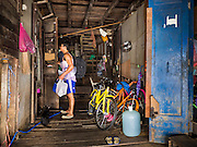 05 OCTOBER 2015 - BANGKOK, THAILAND:  A man being evicted looks into his room before closing the door for last time in the Wat Kalayanamit neighborhood. Fifty-four homes around Wat Kalayanamit, a historic Buddhist temple on the Chao Phraya River in the Thonburi section of Bangkok, are being razed and the residents evicted to make way for new development at the temple. The abbot of the temple said he was evicting the residents, who have lived on the temple grounds for generations, because their homes are unsafe and because he wants to improve the temple grounds. The evictions are a part of a Bangkok trend, especially along the Chao Phraya River and BTS light rail lines. Low income people are being evicted from their long time homes to make way for urban renewal.        PHOTO BY JACK KURTZ