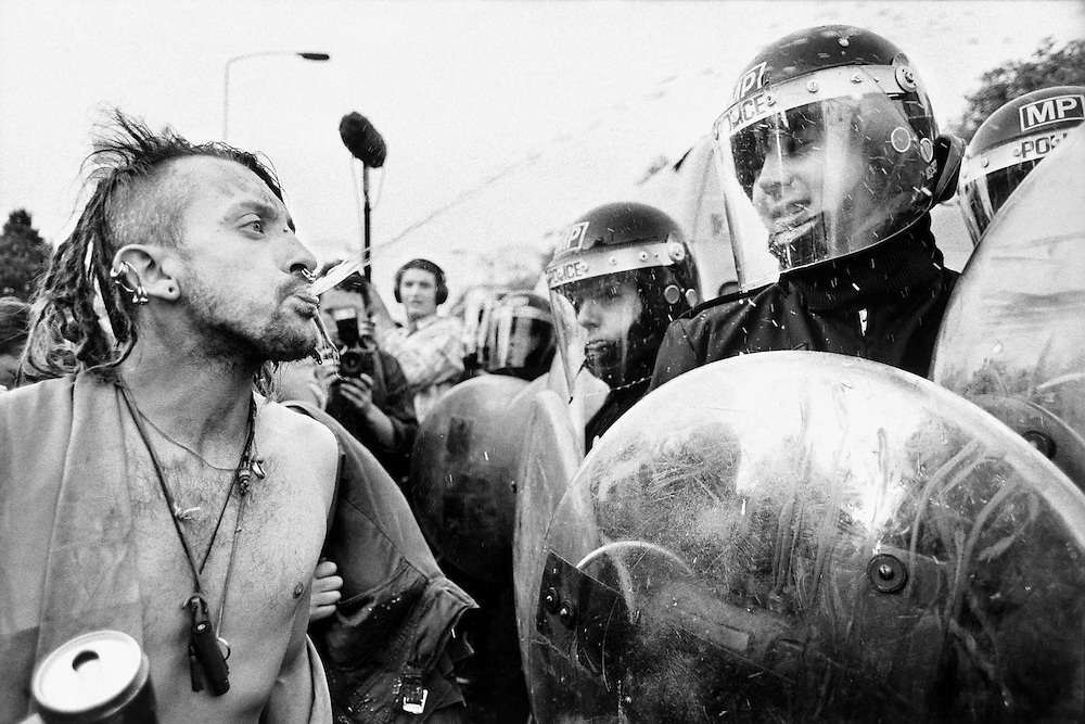 Protester spiting beer at a policeman during a protest against, the criminal justice bill. London.