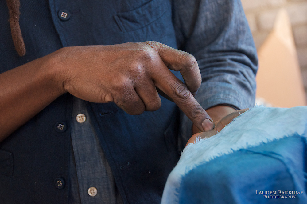 Demonstrating the difference in color between three and one dip in the indigo vat. Indigo dye and bogolan workshop held with Aboubakar Fofana in Johannesburg, South Africa