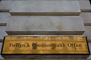 Detail of the brass nameplate outside the Foreign & Commonwealth Office outside the government department on King Charles Street SW1, on 5th October, 2017, in London, England. The main Foreign Office building is in King Charles Street, and was built by George Gilbert Scott in partnership with Matthew Digby Wyatt and completed in 1868 as part of the new block of government offices which included the India Office and later 1875 the Colonial and Home Offices. George Gilbert Scott was responsible for the overall classical design of these offices but he had an amicable partnership with Wyatt, the India Office's Surveyor, who designed and built the interior of the India Office.