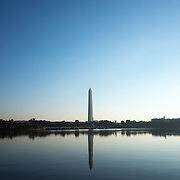 The Washington Monument reflected on calm waters of the Tidal Basin in Washington DC. Built to honor George Washington, the country's first president, the 555-foot marble obelisk towers over Washington DC and stands in the center of the National Mall.