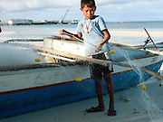 Gunray Villarosa (11) helps his brother prepare fishing nets before going fishing, Talisay; Santa Fe, Bantayan Island, The Philippines. On November 6 2013 Typhoon Haiyan hit the Philippines and was one of the most powerful storms to ever make landfall. The storm had a devastating impact on the fishing and seaweed industry and caused extensive environmental damage which will have a long term impact on ecosystems and the communities who rely on them for food and employment. Three-quarters of the island's population of about 136,000 depend on fishing as their main source of income. Thousands lost their boats and equipment in the storm. Oxfam is working to support the immediate and long-term needs of affected communities on Bantayan Island including establishing boat repair stations in Bantayan.