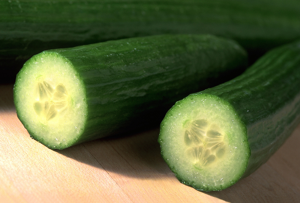 Close up photograph of a group of English Cucumbers on a butcher block table with one cut in half to expose the interior