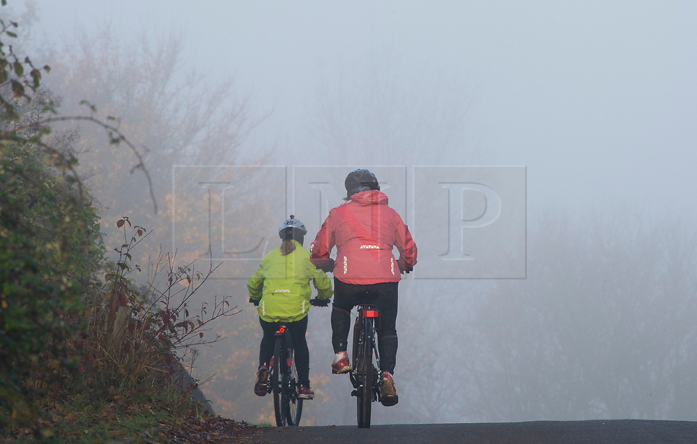 © Licensed to London News Pictures. 05/11/2020.  <br /> Eynsford, UK. Two cyclists riding into the fog in Eynsford, Kent. Freezing cold foggy weather conditions as temperatures drop to -3 in some parts of the UK. Photo credit:Grant Falvey/LNP