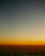 Los Angeles basin cityscape with crescent moon in sky at night