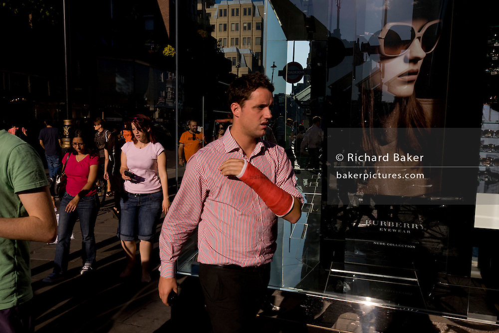 A young man with a red cast passes-by a poster girl for Burberry sunglasses they call Eyewear, in a sunlit London street. Burberry Group plc is a British luxury fashion house, manufacturing clothing, fragrance, and fashion accessories.
