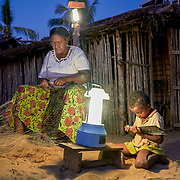 """Yollande Randrianambinina fixes a fishing net in front of a solar lamp while her grand-daughter studies. Dubbed the """"Solar Mamas,"""" Randrianambinina and her friends were the first in their village to join a program by the World Wildlife Fund (WWF) to become electric engineers capable of installing and repairing solar panels. <br /> Across much of this African nation, where 77% of the population of 21 million has no access to electricity -- a figure rising to a staggering 94% among the rural population  -- nighttime means the burning of kerosene lamps and diesel engines, which fill the houses with toxic smoke. And it means the destruction of forests for firewood in one of the world's most biologically-diverse habitats. <br /> <br /> Darkness also brings the threat of crime, violence and accidents.<br /> <br /> Madagascar is the world's forth largest island off the coast of east Africa."""