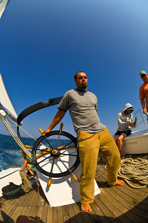 Crew member steers the wheel as the boat is heeling in the wind, Schooner Nathaniel Bowditch, Penobscot Bay, Maine USA