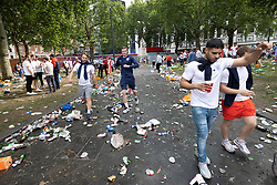© Licensed to London News Pictures. 11/07/2021. London, UK. England supporters walk through a litter strewn Leicester Square after police stopped people entering in central London on the day of the final of EURO 2020 at Wembley where England will play Italy. Photo credit: Peter Macdiarmid/LNP