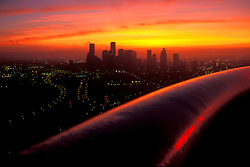 Aerial view ofHouston, Texas skyline with city lights and colorful sunset.