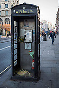 Vomit in a black phone box filled with flowers on The Strand, Central London, United Kingdom. Only telephone boxes owned by BT British Telecom can be the iconic red colour, hence this one being black.
