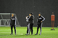 Swansea Manager Garry Monk ® looks on in the rain during Swansea city FC team training in Landore, Swansea, South Wales on Wed 19th Feb 2014. the team are training ahead of tomorrow's UEFA Europa league match against Napoli.<br /> pic by Phil Rees, Andrew Orchard sports photography.