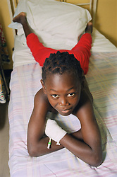 Young patient with bandaged hand lying on bed on children's medical ward,
