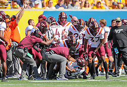 Sep 18, 2021; Morgantown, West Virginia, USA; Virginia Tech Hokies linebacker Alan Tisdale (34) recovers a fumble and celebrates with teammates and coaches during the fourth quarter against the West Virginia Mountaineers at Mountaineer Field at Milan Puskar Stadium. Mandatory Credit: Ben Queen-USA TODAY Sports