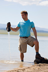 man pouring water out of a hiking boot from a lake