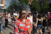 Woman vaping along Oxford Street in London, England, United Kingdom. This is the busiest shopping district in the capital with Oxford Street being the most crowded. Crowds can be so big that many people avoid the area altogether.