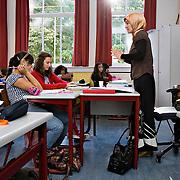 Nederland Rotterdam 23-09-2009 20090923 Serie over onderwijs, het Libanon Lyceum Kralingen,  openbare scholengemeenschap voor mavo, havo en vwo.   Allochtone lerares met hoofddoekje geeft les, leerlingen  maken klassikaal oefeningen, multiculturele samenstelling                                                    .Foto: David Rozing