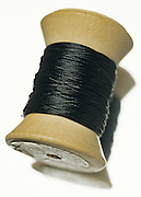 still life of wooden spool of black thread