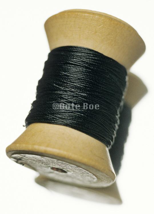 still life of wooden spool of black thread
