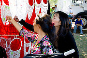 Hmong women looking at fancy necklaces at concession stand. Hmong Sports Festival McMurray Field St Paul Minnesota USA