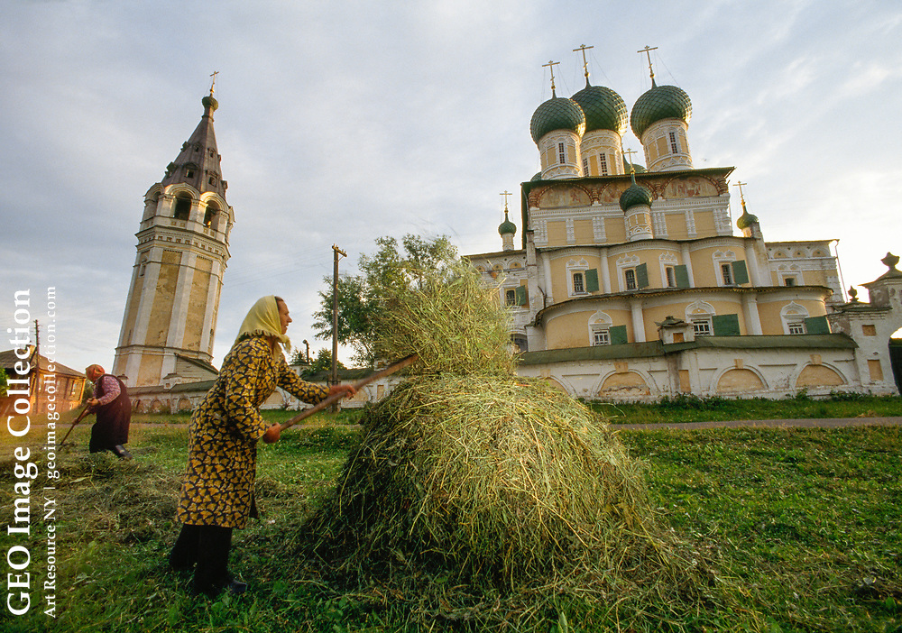 The brick Voskresenskiy Sobor (Cathedral) and bell tower, photographed with a w ide-angle lens; in front of it, women rake grass for hay.  The church's main ic on has a reputation for miracle making:  Lost during the Russian Revolution, it is said to have spawned a spring where the icon was later found.  The church has been in c ontinuous use, even during the Stalin era. Religion is being reborn all over Ru ssia now that the Soviets are out of power; and this church in particular, buil t in 1652, is a landmark on the Volga.