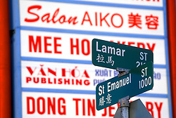 Stock photo of a close up of street signs displayed in two languages with advertising signs in the background