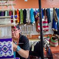Gilbert Begay works away on a weaving at <br /> Weaving in Beauty in Gallup Saturday.