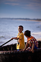 Kids playing with a coracle boat on China Beach near Hoi An, Vietnam.