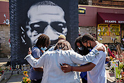 """15 AUGUST 2020 - MINNEAPOLIS, MINNESOTA: People pray in front of a large portrait of George Floyd in front of Cup Foods at the George Floyd Memorial in Minneapolis. Floyd, an unarmed Black man, was killed by Minneapolis police officers of May 25 in front of Cup Foods, a convenience store at the intersection of 38th and Chicago Ave. His killing sparked a week of violent protests across the country. The intersection where he was killed is still closed and has become an unofficial memorial visited by hundreds of people every day. Saturday, more than 100 people gathered at the memorial to demand the city preserve the memorial. On Saturdays in August, the intersection has a market, with venders selling Afro-centric merchandise. The city of Minneapolis had planned to start reopening the intersection as soon as Monday Aug. 17, but delayed those plans indefinitely on Friday, Aug. 14. City residents have created a """"George Floyd Zone"""" at the intersection. They're demanding the recall of Hennepin County Attorney Mike Freeman, requiring Minneapolis police officers have their own private liability insurance, and the allocation of funds for businesses and residents in the community. The city is considering officially renaming Chicago Ave. between 37th and 39th """"George Floyd Jr. Place.""""     PHOTO BY JACK KURTZ"""
