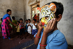 RENUBALA KEI is the teacher in the preschool in ICHHAPUR village.  The teacher is leading the class in a fun game of animal sounds and activities. PINKI PAHAN 5 years is wearing the mask. They are sitting in the semi derelict room beside the  small class room. This is one of many supported kindergartens that PREM works with in villages in Orissa and Andhra Pradesh states of India.