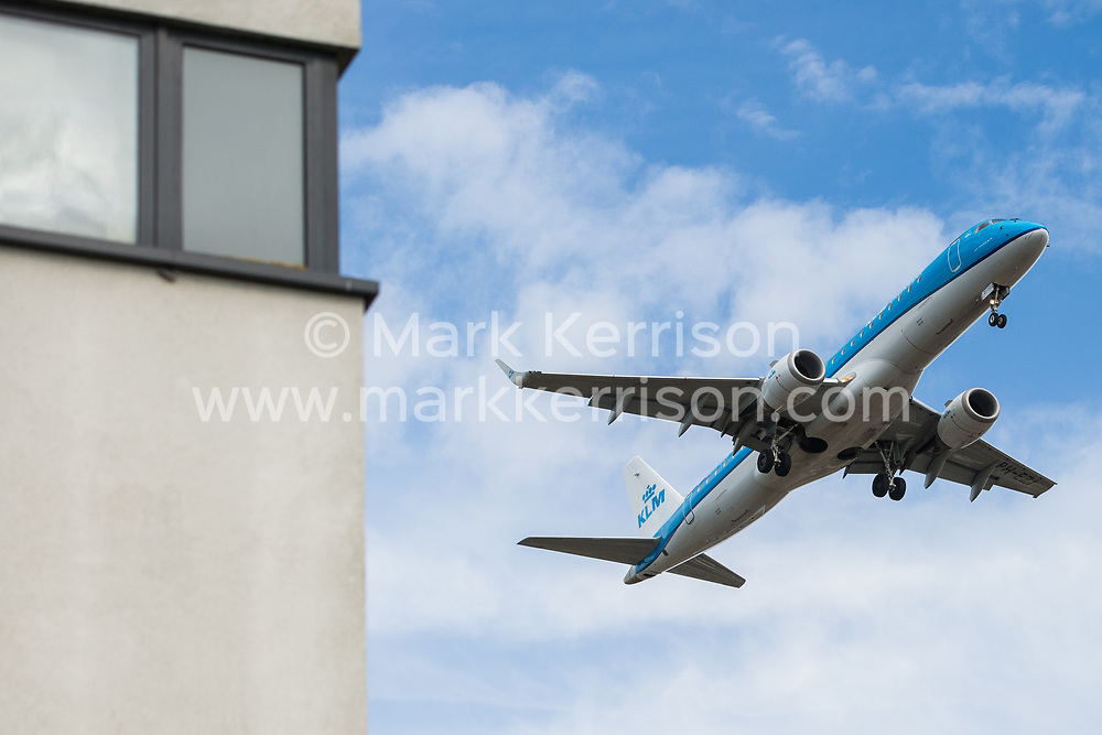 """London, UK. 17 June, 2019. An aircraft on the final approach to Heathrow airport passes alongside a building in Hounslow. On 18th June, Heathrow will publish its airspace and future operations consultation on its """"master plan"""" for Heathrow expansion following approval in principle of a third runway by MPs last year. Heathrow is expected to increase the number of flights from the current cap of 480,000 per year imposed when Terminal 5 was built to 505,000 per year in 2021 and to 740,000 per year should a third runway be constructed."""
