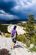 Climber on Marmot Dome watching storm over Tuolumne Meadows, Yosemite National Park, California USA