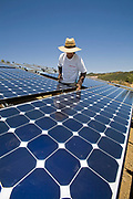 Green workers install a residential grid-tied solar array on a hillside in Malibu, Installation by Martifer Solar USA, California, USA