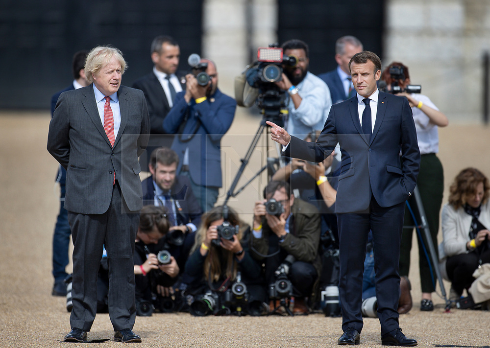 © Licensed to London News Pictures. 18/06/2020. London, UK. President Macron (R) and Prime Minister Boris Johnson wait on Horse Guards Parade for a fly past by the Royal Air Force (RAF) Red Arrows and the Patrouille de France (PAF), the aerobatics demonstration team of the French Air Force takes place over central London. Today's events commemorate the 80th anniversary of the Second World War resistance leader General Charles de Gaulle's historic broadcast to occupied France on June 18, 1940. Photo credit: Peter Macdiarmid/LNP