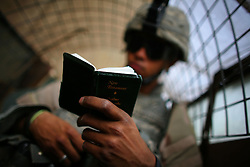 A machine gunner with Charlie Co. 1-26 Infantry 1st Infantry Division reads from a small copy of the New Testament before heading out on patrol in Adhamiya on Sunday April 29, 2007.