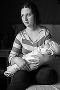 Crina Sarda, Romanian Kalderash Roma and EU migrant, sitting in a borrowed apartment in Sweden with her swaddled baby son in her lap