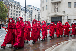 London, UK. 11 October, 2019. The Red Brigade passes in front of the BBC's New Broadcasting House after joining climate activists blocking the main entrance to the building on the fifth day of International Rebellion protests. The activists were demanding that the broadcaster 'tell the truth' regarding the climate emergency.