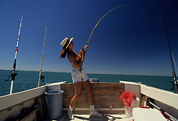 Stock photo of woman reeling in a fish from the side of a fishing boat