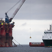 Greenpeace activists board a BP oil rig in Cromarty Firth to stop it from further oil drilling at sea, June 10th 2019, Cromarty, Scotland, United Kingdom. The oil rig 'Paul B. Loyd, Jnr', owned by Transocean, was due to head to BP's Vorlich field, 150 miles (241km) east of Aberdeen to drill for oil for BP. Oil rig crew comes off the rig by crane. The occupation by Greenpeace activists subsequently delayed the departure for 5 days and 14 activists were arrested in the process. Greenpeace says that in an age of climate emergency BP should not be drilling for new oil but look for non-fossil fuel means of energy.