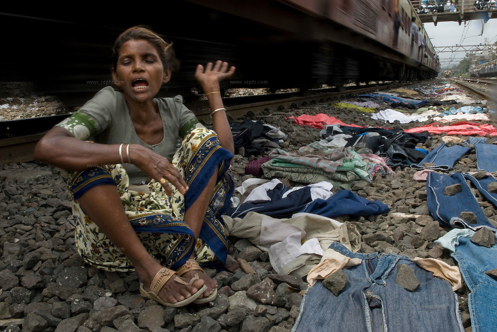 A dhobi woman waits for a train to pass as she looks after her washing lying to dry on the Central Line tracks.