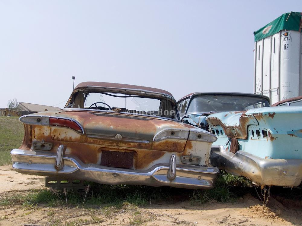 classic cars sitting in a junkyard