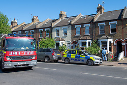 © Licensed to London News Pictures. 25/04/2020. London, UK. Forensic investigators, a fire engine and a police vehicle at the scene of a fatal house fire. A man has died in a house fire in Earlsfield, Wandsworth. Firefighters found the man in a ground floor bedroom. He was brought out of the property by fire crews but he died at the scene. London Fire Brigade was called at 07:36 BST and the fire was under control by 08:33 BST. Photo credit: Peter Manning/LNP