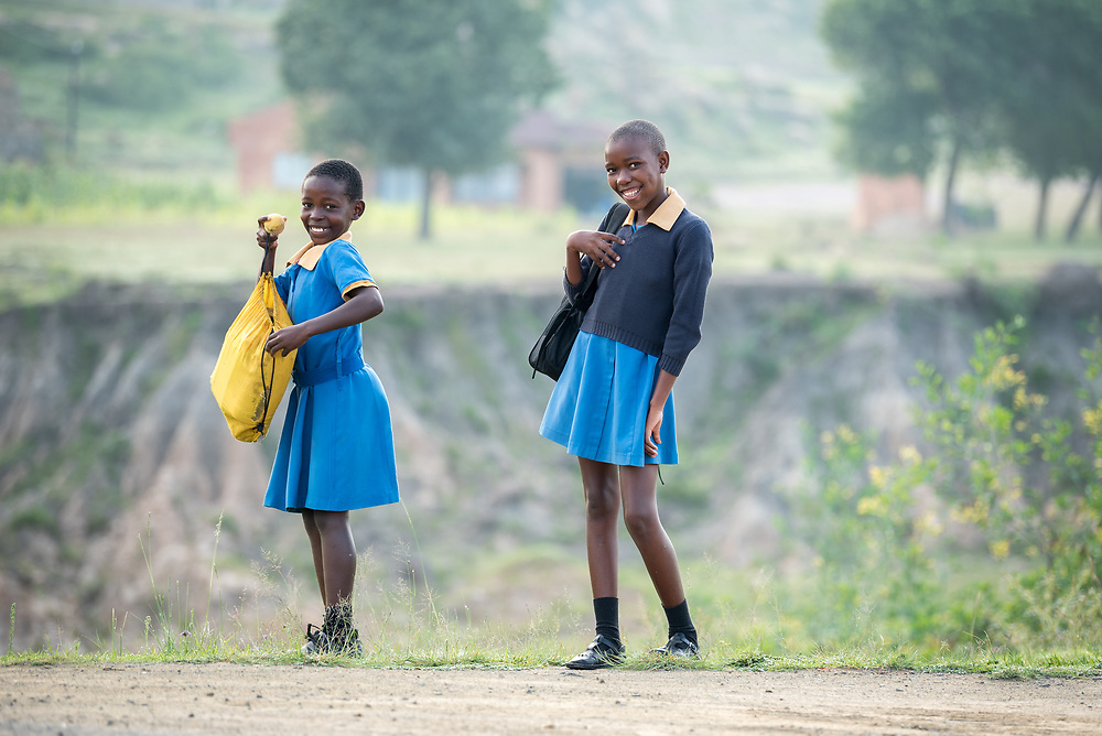 1 March 2017, Thaba Bosiu, Lesotho: Girls on the way to Thaba Bosiu Primary School, a public school accommodating some 100 children in Thaba Bosiu, Lesotho. To the left, Khodliso, and to the right, Mokho. Thaba Bosiu is a sandstone plateau some 24 kilometers east of Lesotho's capital, Maseru. The name means Night Mountain, and surrounding the plateau is a small village and open plains. Thaba Bosiu was once the capital of Lesotho, and the mountain was the stronghold of the Basotho king when the kingdom of Lesotho was formed.