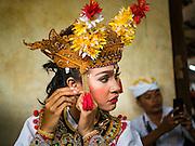 19 JULY 2016 - TAMPAKSIRING, GIANYAR, BALI, INDONESIA:  A dancer gets ready to perform on the first day of a ceremony to honor the anniversary Pura Agung temple, one of the most important Hindu temples on Bali. This year's ceremony is the most important in years because it falls on the 50 year cycle of the temple's founding. This year's ceremony lasts for 11 days.     PHOTO BY JACK KURTZ