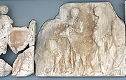 Three youths wearing cloaks lead four rams.  A fragment probably belongs to the body of the first. The other two are conversing while resting one hand on the back of the animals they are leading to sacrifice.  Behind them is a marshal. He turns back to face the procession. From the friezes around the Parthenon in Athens, Greece. 5th century BC