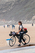 Female tourist on cycling tour with her bicycle on the beach of Nazare, Portugal