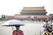 A Chinese woman protects herself from the sun's rays using an umbrella and a scarf in Tiananmen Square in Beijing, China, July 19, 2014. <br /> <br /> Pale skin has historically been prized as beautiful in China, and the concept is widespread in other Asian countries. Besides health topics, beauty is one of the main reasons that makes protection from the sun's rays so important. <br /> <br /> © Giorgio Perottino