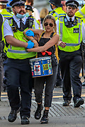 Police officers drag a handcuffed climate activist drummer from the Extinction Rebellion to walk after they had arrested her during the group's 'Impossible Rebellion' series of actions at Oxford Circus in central London, on Wednesday, August 25, 2021. - Climate change demonstrators from environmental activist group Extinction Rebellion continued with their latest round of protests in central London, promising two weeks of disruption. (VX Photo/ Vudi Xhymshiti)